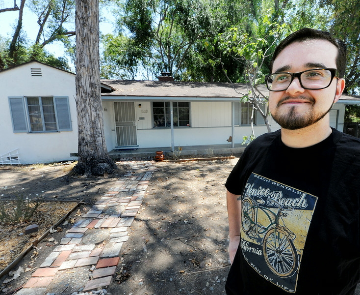 Description of . Joel Alvarez standing in front of a Caltrans home that he has rented for three years at 532 Meridian Avenue in South Pasadena.  Alvarez who like the City of South Pasadena and its excellent schools is looking forward to having the opportunity to  purchase that home from Caltrans Tuesday, July 8, 2014. Fifty-three properties owned by Caltrans have gone back on the market after years of being state-owned rentals. The properties were once reserved to be demolished for the possible 710 freeway extension, but Caltrans now says they are outside the footprint of the five remaining options being studied by the agency to complete the freeway. Caltrans was also prompted to sell the homes by a state law passed last year.(Photo by Walt Mancini/Pasadena Star-News)
