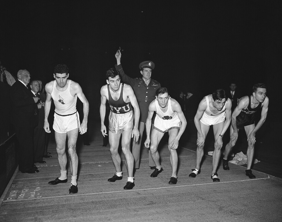 """Description of . Runner's toe the starting line as Capt. Louis S. Zamperini (standing behind) prepares to start the field in the special invitation mile run named in his honor at the IC4A indoor track and field championships on March 2, 1946 in Madison Square Garden, New York. The entries are (left to right) Tommy Quinn, New York Athletic Club; Leslie MacMitchell, of New York, William J. McGuire, Jr., 69th regiment A.A.; Marcel Hansenne, French track star, and Forest C. Efaw, of Okla., unattached. MacMitchell won the race. The mile run was named in Zamperini's honor a year ago when he was listed as """"officially dead"""" by the War Department. (AP Photo/MZ)"""