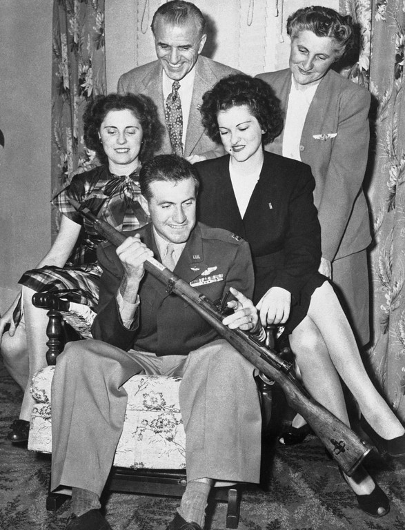 Description of . Capt. Louis Zamperini (seated), former Japanese prisoner of war and Olympic distance runner, shows his family a Japanese rifle at a long-delayed Christmas Party which was held on his return to his home in Torrance, Calif., on Oct. 6, 1946. Zamperini, an army bombardier, spent 47 days on a life raft and then 28 months in Japanese prison camps. Left to right: A sister, Mrs. Sylvia Flammer; father, Anthony Zamperini; a sister, Virginia Zamperini and mother, Louise. (AP Photo/LA)