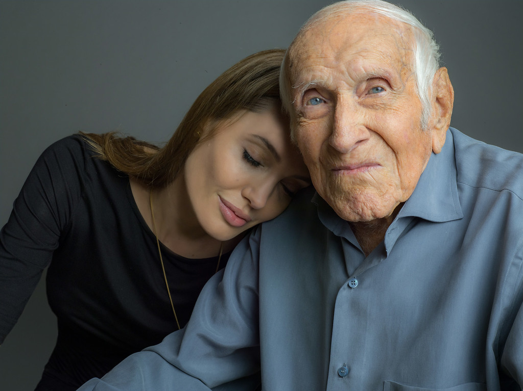Description of . This undated photo provided by Universal Pictures, Angelina Jolie is photographed with Louis Zamperini. Zamperini, a U.S. Olympic distance runner and World War II veteran who survived 47 days on a raft in the Pacific after his bomber crashed, then endured two years in Japanese prison camps, died Wednesday, July 2, 2014, according to Universal Pictures studio spokesman Michael Moses. He was 97.  Jolie is directing the Universal movie,