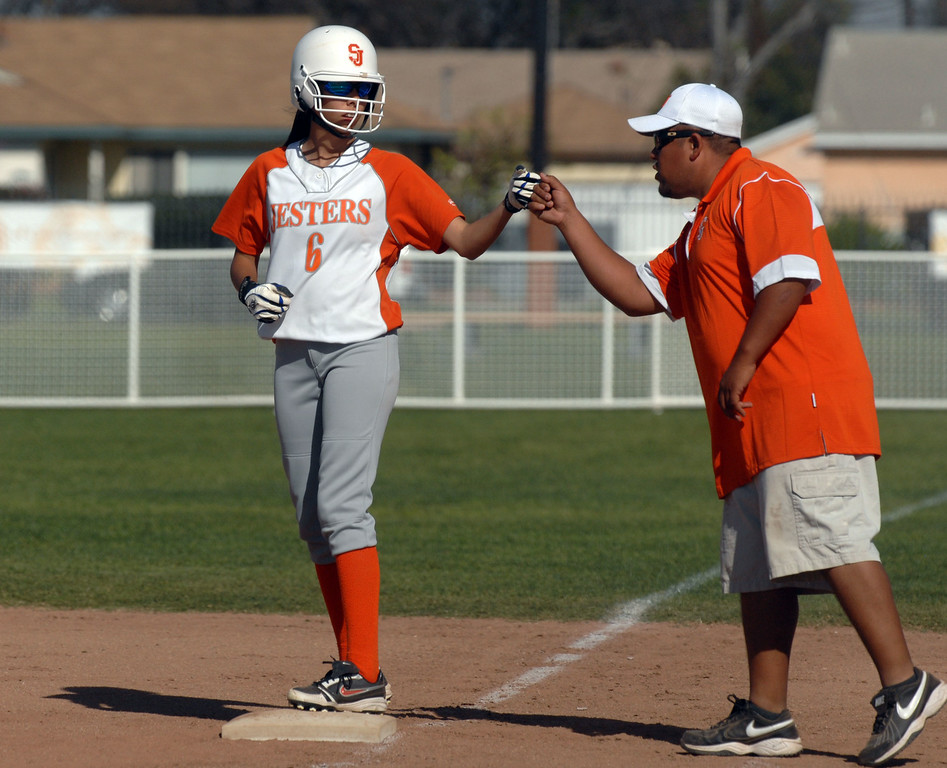 Description of . 3/29/10 - St. Joseph's Yasmin Cruz gets a fist bump from her coach at first base during a game against St. Paul on Monday afternoon. The Jesters won 7-1.