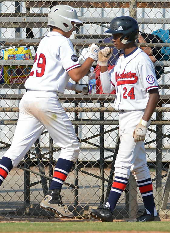 Description of . Westchester's Nick Goff (24) bumps fists with Matthew Kanfer as they begin the scoring in the first inning against Torrance in a Babe Ruth final at Kendall Park in Torrance Thursday. Westchester won the first game 6-5.