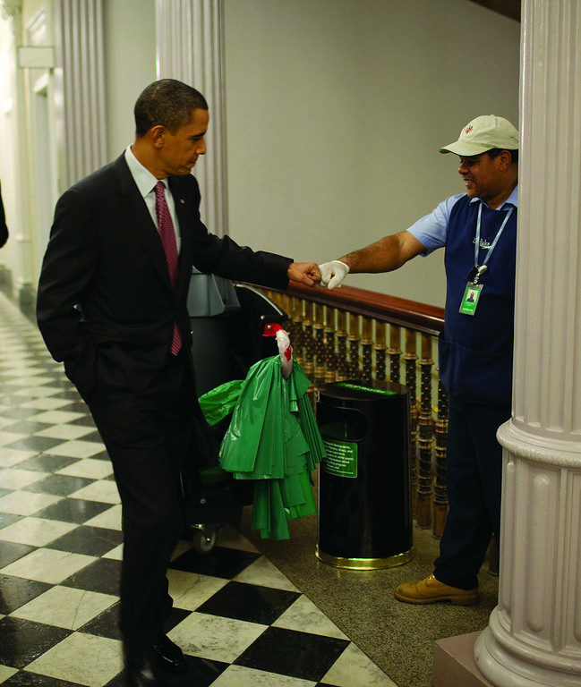 Description of . President Barack Obama fist-bumps AbilityOne custodian, Lawrence Lipscomb, in a federal office building following the opening session of the White House Forum on Jobs and Economic Growth. Credit: Official White House Photo by Pete Souza.  (PRNewsFoto/AbilityOne, Pete Souza)