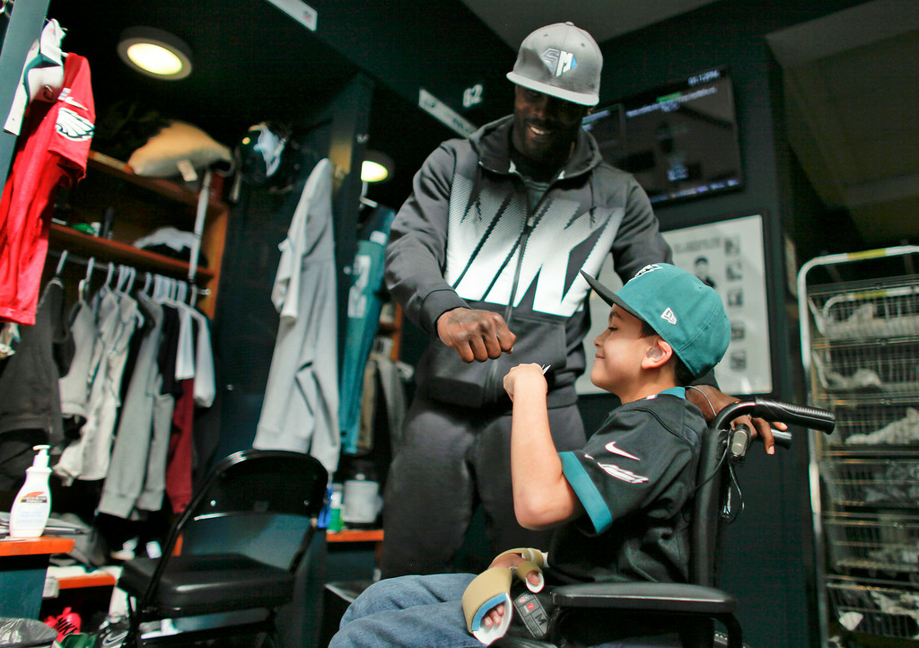 Description of . Philadelphia eagles quarterback Michael Vick give seven-year-old Justin Perales  a fist bump during a tour of the Eagles training facility in Philadelphia. Four years after his release from prison, Vick is one of the NFL's most active players involving charities. Though he's no longer the starting quarterback for the Eagles, he's unquestionably the team leader.  (AP Photo/ Joseph Kaczmarek)