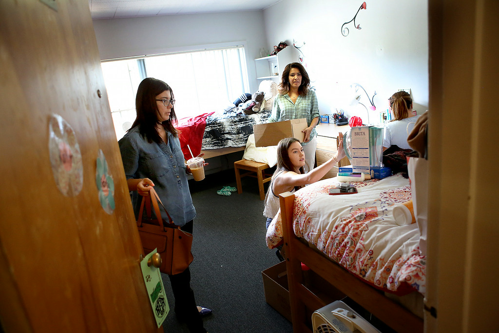 Description of . University of La Verne incoming freshman Sabrina Leeper, at center, unpacks some of her belongings, with help from her godmother Annette Ramos, at left, her aunt Ann-Marie Torres, and mom Andrea Leeper, on move-in day,Wednesday August 20, 2014,  as students prepare for the new fall semester at the University of La Verne, in August 2014.  (Nancy Newman/for the Inland Valley Daily Bulletin)