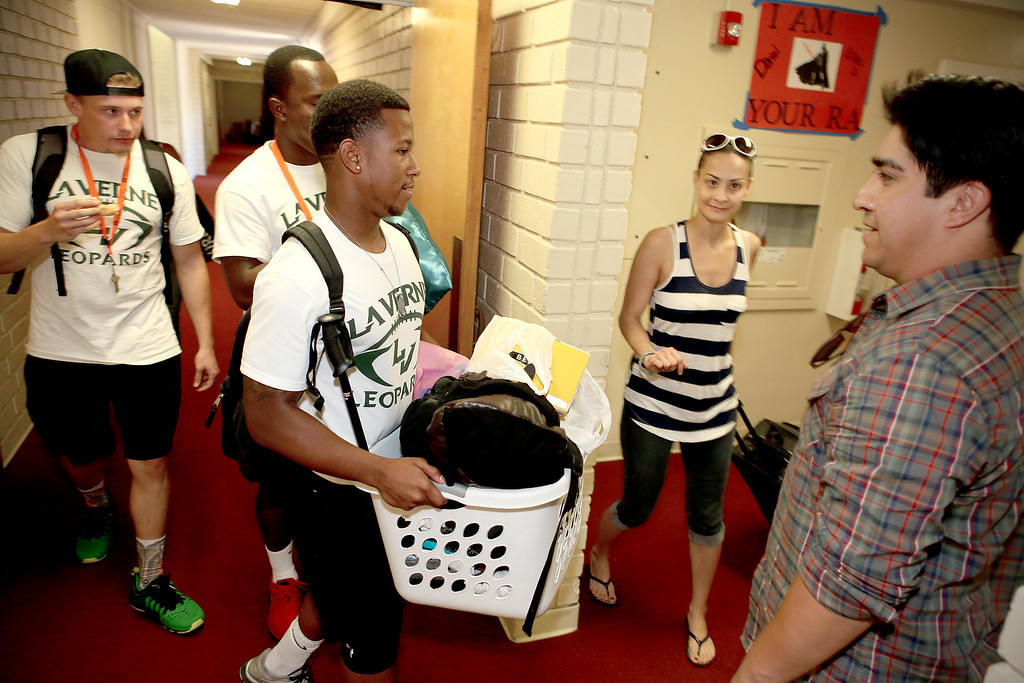 Description of . University of La Verne football player George Evans lll, volunteers along with his teammates on move-in day, by helping new students bring their belongings into the dorms, Wednesday August 20, 2014, in preparation for the new fall semester at the University of La Verne, in August 2014.  (Nancy Newman/for the Inland Valley Daily Bulletin)