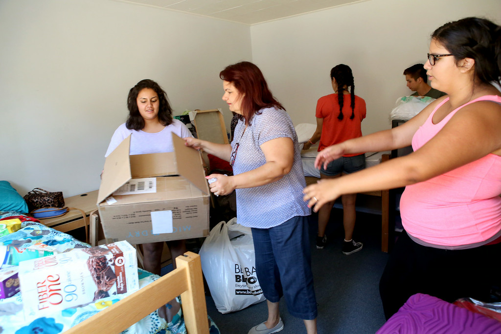 Description of . Incoming freshman Valeria Pineda, at left, gets some help from her mom, Elsie Howard, and sister Victoria Pineda, at right, as they set up her dorm room Wednesday August 20, 2014.  Students spent the day moving into the dorms, in preparation for the new fall semester at the University of La Verne, in August 2014.  (Nancy Newman/for the Inland Valley Daily Bulletin)