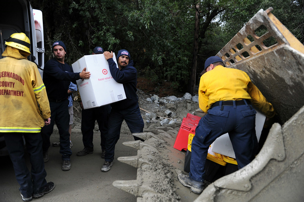 Description of . Red Cross supplies are placed onto a loader to take to residents during clean up efforts on Monday, August 4, 2014 in Forest Falls, Ca. (Micah Escamilla/San Bernardino Sun)