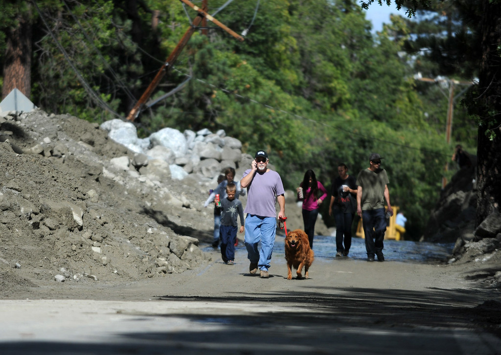 Description of . Mick Gibson, of Forest Falls, walks his dog, Amy, on Valley of the Falls Road after it re-opened on Monday, August 4, 2014 in Forest Falls, Ca. (Micah Escamilla/San Bernardino Sun)