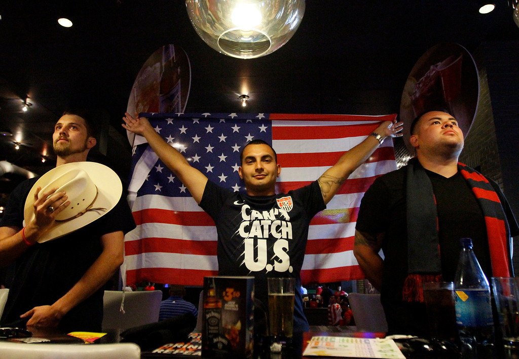 Description of . Tony Aguro, center, of Riverside, holds the American flag as the national anthem plays during the USA vs Ghana World Cup soccer match on Monday, June 16, 2014 at Dave and Busters in Ontario, Ca. (Micah Escamilla/Inland Valley Daily Bulletin)