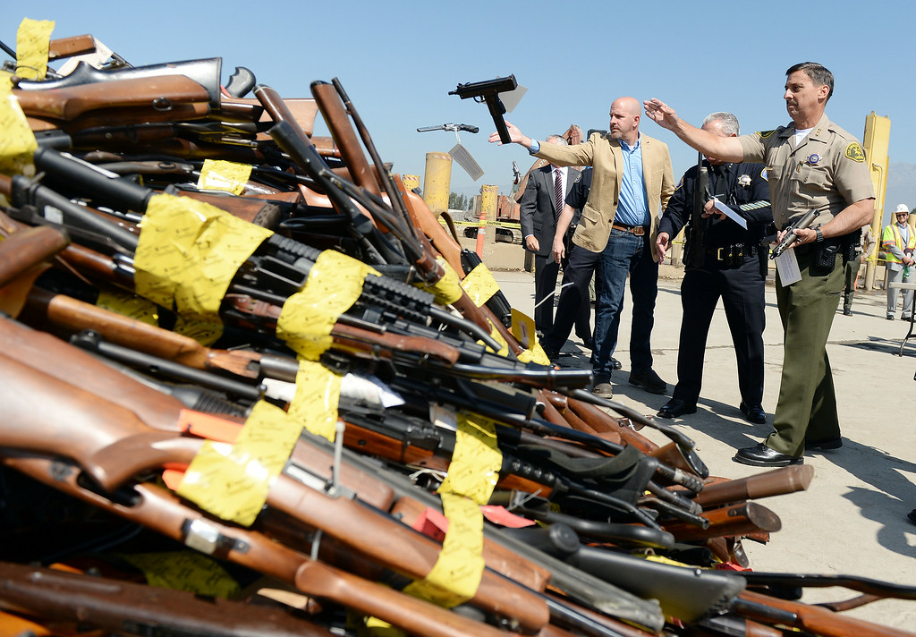 Description of . Los Angeles County Assistant Sheriff Todd Rogers throws a confiscated hand gun into a pile at Gerdau Steel Mill in Rancho Cucamonga Wednesday August 13, 2014. Approximately 4,700 weapons confiscated amongst 12 Los Angeles County law enforcement agencies were melted down into steel.   (Will Lester/Inland Valley Daily Bulletin)