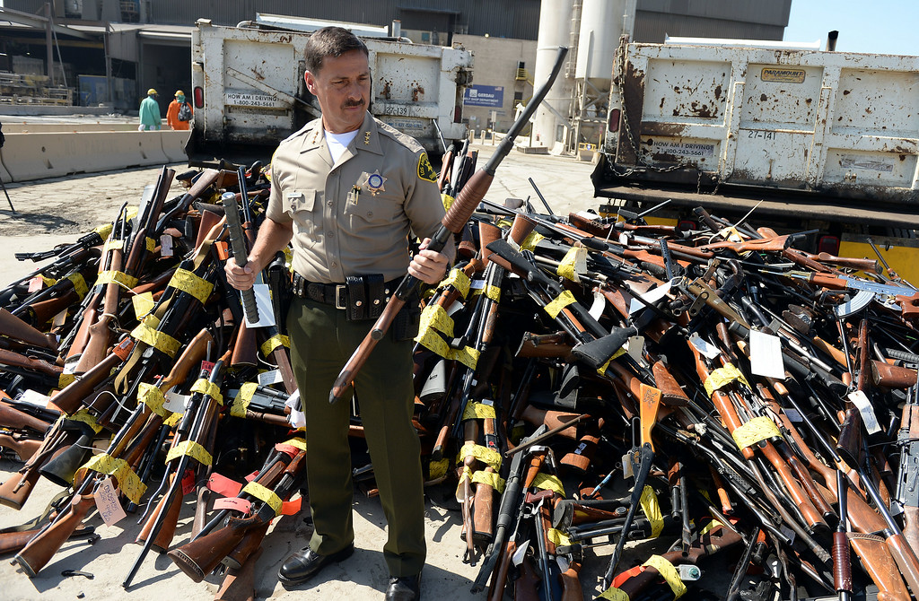 Description of . Los Angeles County Assistant Sheriff Todd Rogers holds a confiscated rifle next to a pile of weapons at Gerdau Steel Mill in Rancho Cucamonga Wednesday August 13, 2014. Approximately 4,700 weapons confiscated amongst 12 Los Angeles County law enforcement agencies were melted down into steel.   (Will Lester/Inland Valley Daily Bulletin)