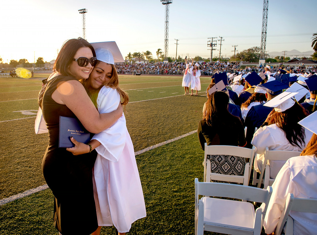 Description of . Montebello High teacher Dayana (cq) Aguilar, left, hugs graduate Alyssa Soneff during commencement June 19, 2014.  (Staff photo by Leo Jarzomb/Whittier Daily News)