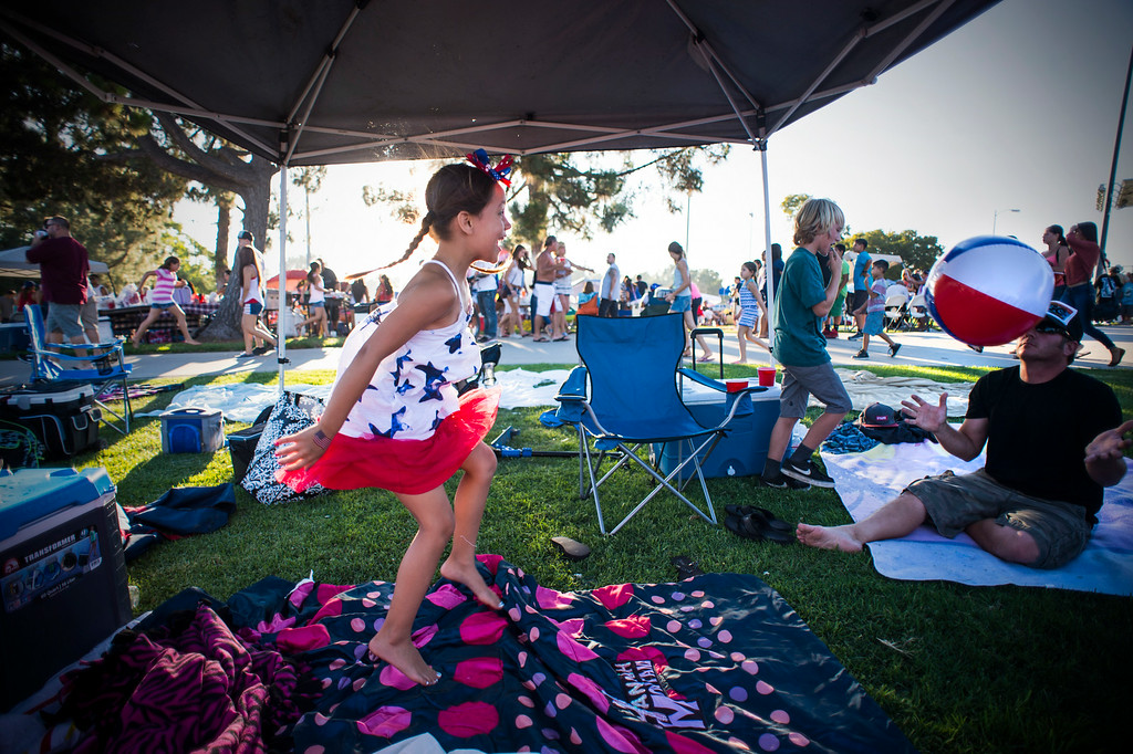 Description of . Baily Mata, 6, plays ball in her family's tent before La Mirada's annual fireworks show and festival Thursday night, July 3, 2014 at La Mirada Regional Park. (Photo by Sarah Reingewirtz/Pasadena Star-News)