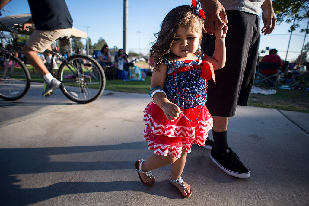 Description of . Dalyla Alvarez, 23 months, holds her father Jesse's hand as she shows her patriotic dress before La Mirada's annual fireworks show and festival Thursday night, July 3, 2014 at La Mirada Regional Park. (Photo by Sarah Reingewirtz/Pasadena Star-News)