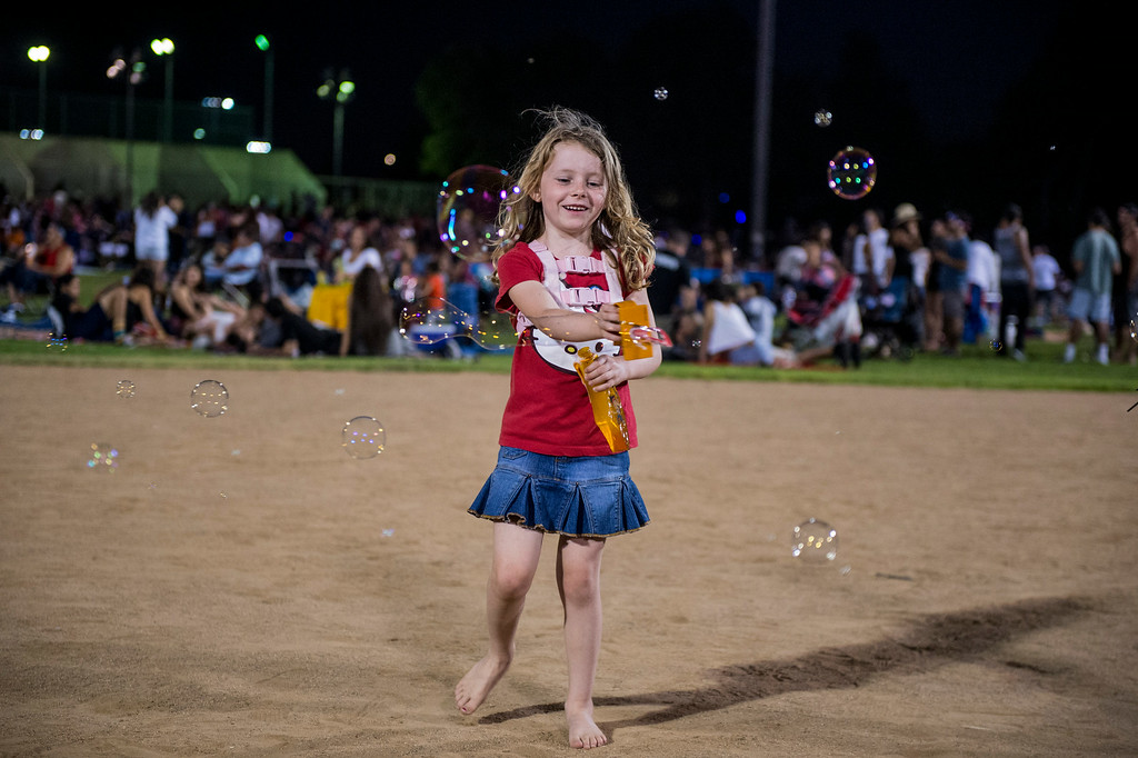Description of . A girl shoots bubbles as she waits for La Mirada's annual fireworks show to begin Thursday night, July 3, 2014 at La Mirada Regional Park. (Photo by Sarah Reingewirtz/Pasadena Star-News)