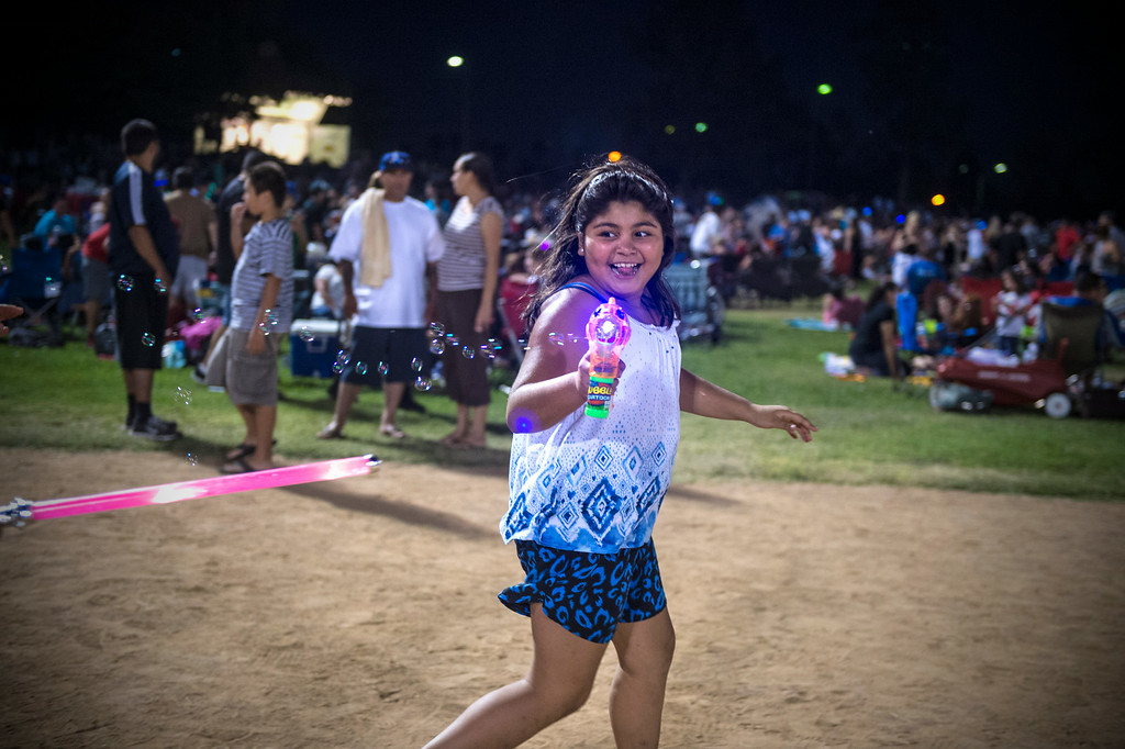 Description of . Isabella Ochoa, 9, of Anaheim, shoots bubbles as she waits for La Mirada's annual fireworks show to begin Thursday night, July 3, 2014 at La Mirada Regional Park. (Photo by Sarah Reingewirtz/Pasadena Star-News)