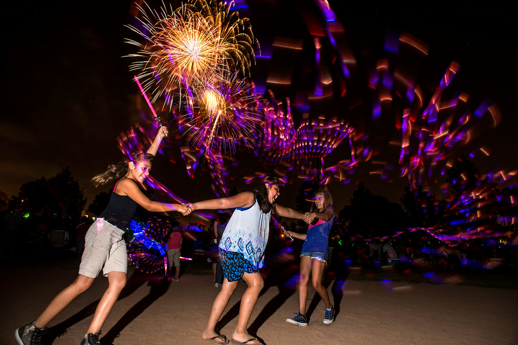 Description of . Cousins, from left, Lenise De La Torre, 8, of Buena Park, Isabella Ochoa, 9, of Anaheim, and Riley Vega, 9, of Buena Park, play with glow sticks during La Mirada's annual fireworks show Thursday night, July 3, 2014 at La Mirada Regional Park. (Photo by Sarah Reingewirtz/Pasadena Star-News)