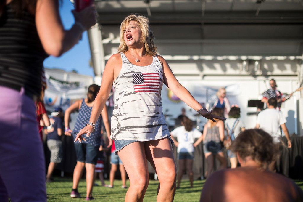Description of . Wendy Fonzeca, who graduated from La Mirada High School in 1983, dances with high school friends to Yard Sale as La Mirada holds their annual fireworks show and festival Thursday night, July 3, 2014 at La Mirada Regional Park. (Photo by Sarah Reingewirtz/Pasadena Star-News)