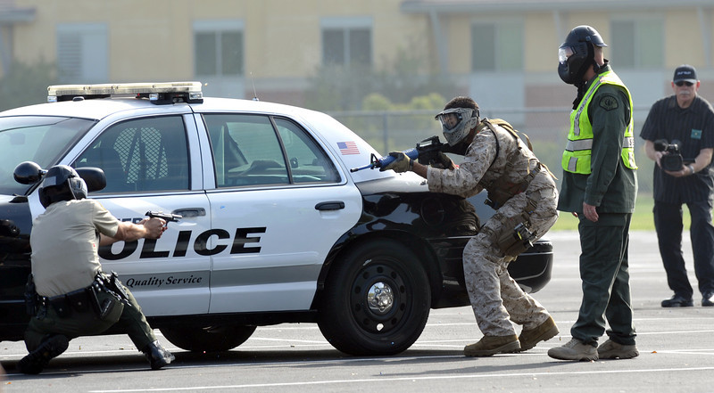 """A training instructor, right, watches as a Sheriff's Deputy, left, encounters a suspect as Biola University hosts an Active Shooter training drill with simulations and less lethal weapons systems at Biola University on Aug. 14 with simulations and less lethal weapons systems on Wednesday August 14, 2013. Training instructors from the Los Angeles County Sheriff's Department Tactics and Survival Training Staff will provide briefing on """"Active Shooter Response and School Safety."""" (Whittier Daily News/Staff Photo by Keith Durflinger)"""