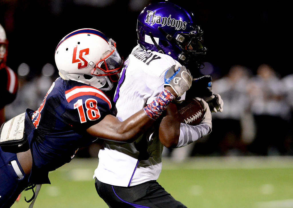 Description of . La Salle's Brandon Mulligan (18) takes down Cathedral's Martaveous Holliday (3) during the first half of Friday night's game at La Salle High School in Pasadena, on August 30, 2013. (Photo by Sarah Reingewirtz/Pasadena Star-News)