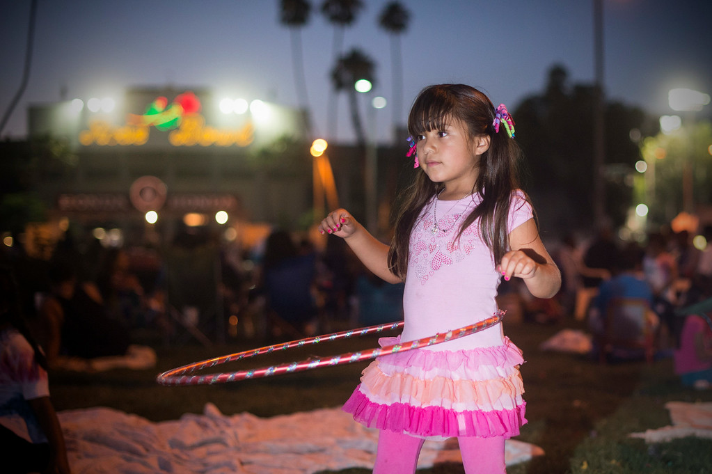 Description of . Yesenia Aviles, 6, uses a Hula Hoop as the Martinez family and friends gather to watch Americafest's annual fireworks show at the Rose Bowl in Pasadena Friday night, July 4, 2014. The Martinez family has gathered every year to see the show to celebrate Sebastian Martinez' birthdays since the 7-year-old was born on the Fourth of July. (Photo by Sarah Reingewirtz/Pasadena Star-News)