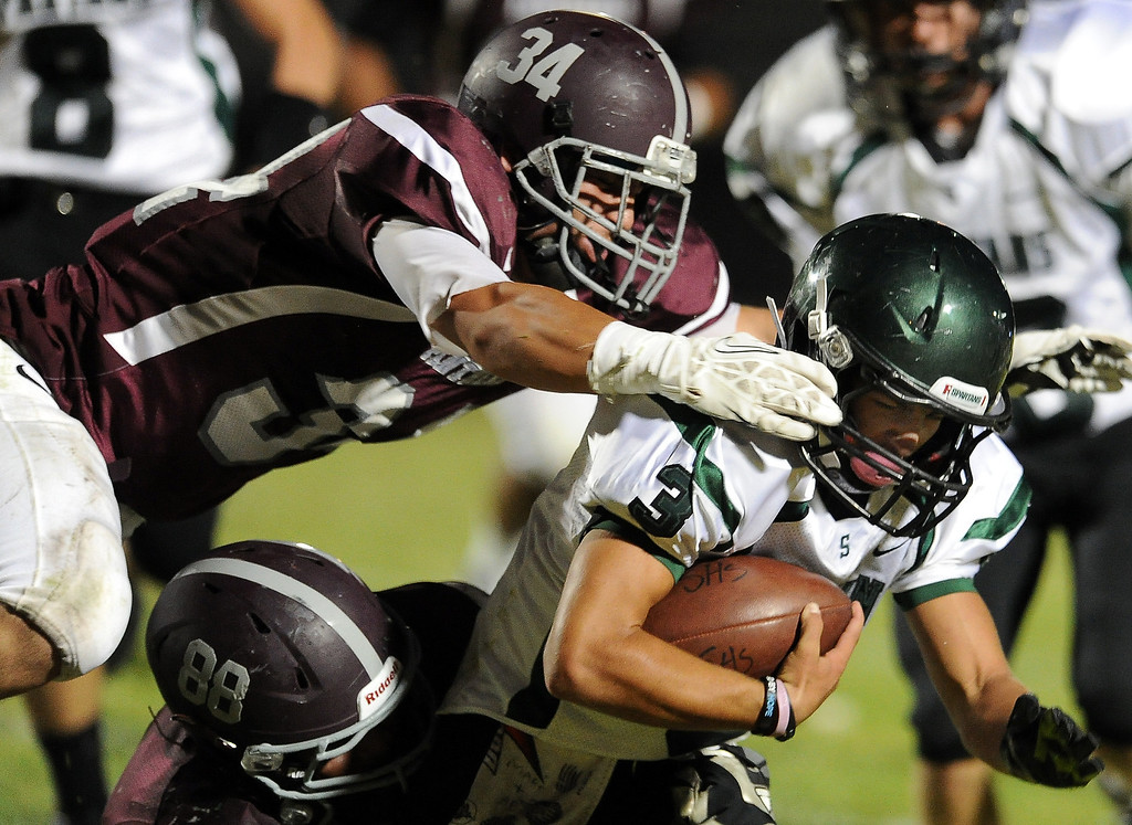 Description of . Rosemead's Michael Sahagun (80) along with Demarco Munoz (52) tackles South Torrance's Anthony Peters (3) for a loss of yards in the first half of a prep football game at Rosemead High School in Rosemead, Calif. on Thursday, Sept. 12, 2013.   (Photo by Keith Birmingham/Pasadena Star-News)