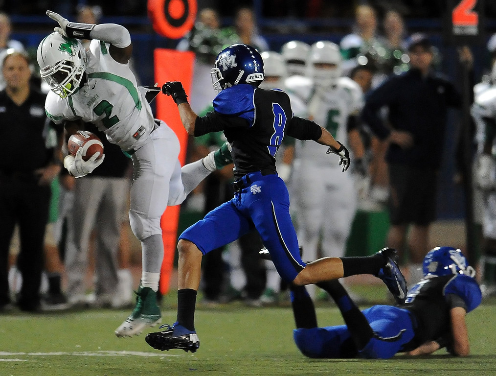 Description of . Monrovia's Kurt Scoby (2) leaps over San Marino's Mark Wicke (4) for a first down in the first half of a prep football game at Monrovia High School in Monrovia, Calif., on Friday, Nov. 8, 2013. 