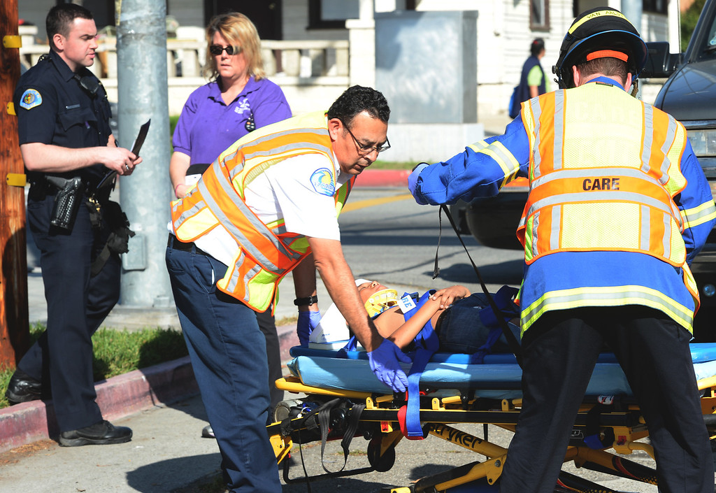 Description of . Los Angeles County fire paramedics and CARE Ambulance personnel respond to a child struck by an SUV on Bailey Street and Pickering Avenue in Whittier on Thursday March 13, 2014. The child was then transported to a trauma center by a Los Angeles County rescue helicopter from Whittier High School. (Staff Photo by Keith Durflinger/Whittier Daily News)