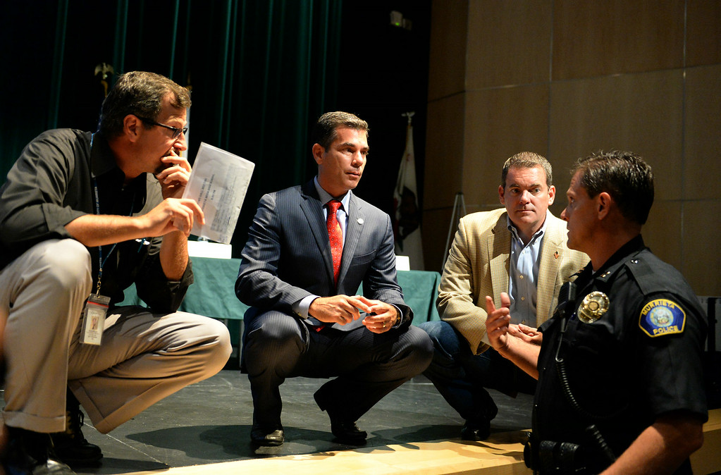 Description of . Murrieta Mayor Alan Long, center, chats with councilman Randon Lane, second from right, and police officer Dennis Vrooman, right, prior to a town hall meeting on Wednesday, July 2, 2014 at Murrieta Mesa High School in Murrieta, Ca. The meeting is being held in response to immigrants who were being processed through a Texas Border Patrol Station and delivered to the Murrieta Border Patrol Station on Tuesday, which created protests from both sides of the immigration issue. (Micah Escamilla/The Sun)