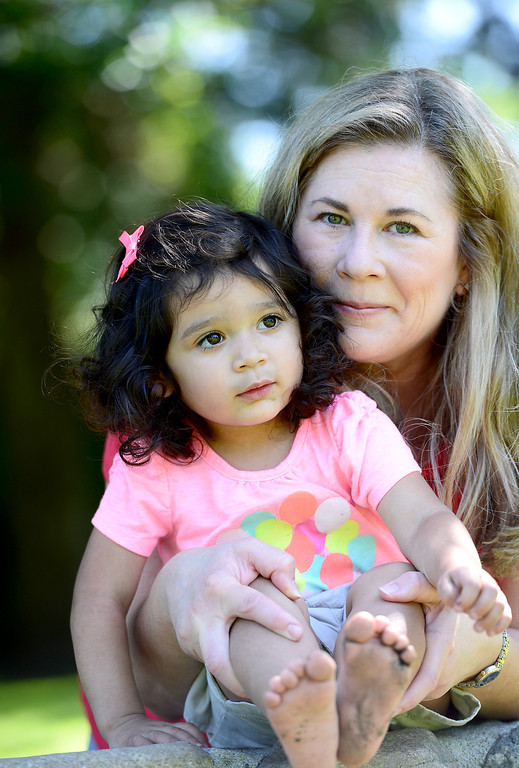 Description of . Suzy Campeau, 51, of South Pasadena, poses with 2-year-old Bella, who she adopted with her husband Greg last December, poses in her neighborhood park Saturday, May 11, 2013. This will be Suzy's first