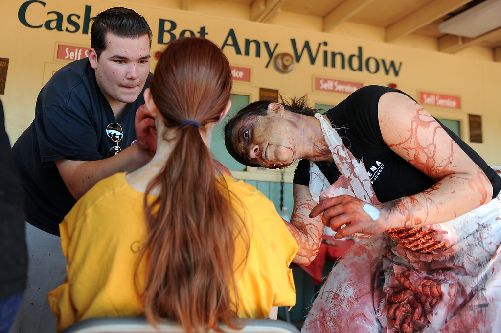 Description of . Thirteen year-old Emily Bonner, center, of Westlake Village has zombie make-up applied by Terrance Kandler, left, Shay Alizadeh, right, during the Zombie Blood Run at Santa Anita Park on Saturday, Aug. 17, 2013 in Arcadia, Calif. The American Red Cross San Gabriel Pomona Valley chapter is partnering with the Zombie Blood Run to prepare the San Gabriel Valley for a disaster, even a zombie apocalypse.  (Keith Birmingham/Pasadena Star-News)
