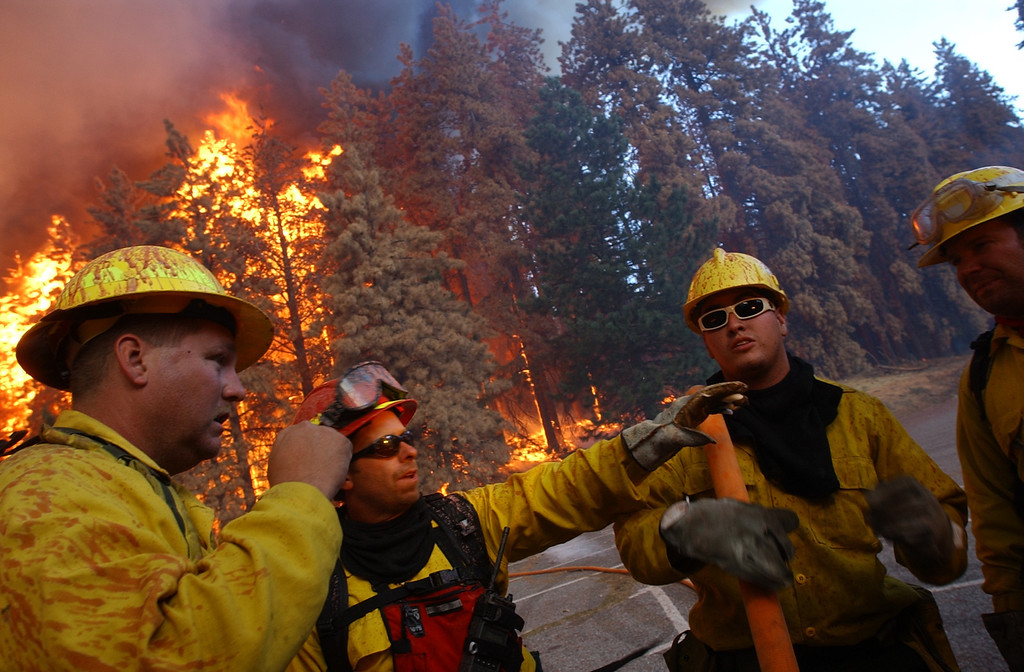Description of . Ten years ago this month the arson caused Old Fire, fanned by Santa Ana winds burned thousands of acres, destroyed hundreds of homes and caused six deaths. The fire burned homes in San Bernardino, Highland, Cedar Glen, Crestline, Running Springs and Lake Arrowhead and forced the evacuation of thousand of residents. Bullhead City, Arizona, firefighters make decisions as fire surrounds them in the parking lot of Santa's Village during the