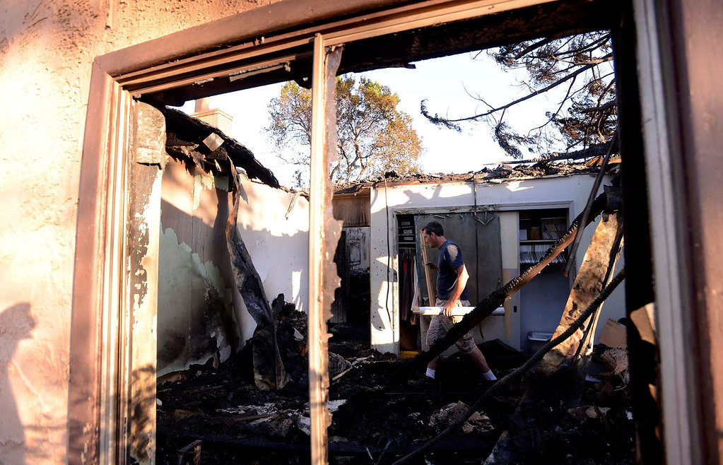 Description of . Michael Kiener, 47, of San Diego, helps to retrieve items from his brother's burned out house along Mesa Road in Banning May 2, 2013.  The Kiener residence was the only structure to burn in the Summit Fire. GABRIEL LUIS ACOSTA/STAFF PHOTOGRAPHER.