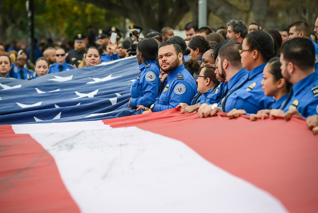 Description of . TSA officers fold a giant US flag at the memorial for slain TSA officer Gerardo Hernandez at the Los Angeles Sports Arena Tuesday, November 12, 2013.  A public memorial was held for Officer Hernandez who was killed at LAX when a gunman entered terminal 3 and opened fire with a semi-automatic rifle.  ( Photo by David Crane/Los Angeles Daily News )