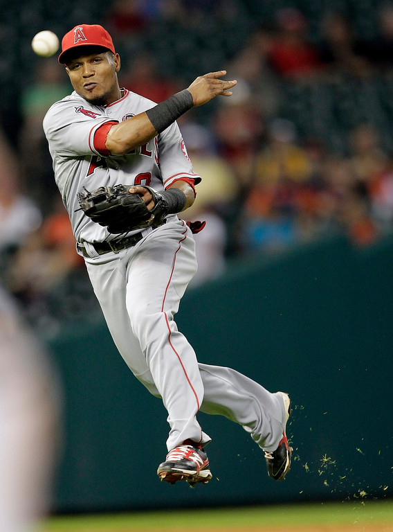 Description of . HOUSTON, TX - SEPTEMBER 14:  Erick Aybar #2 of the Los Angeles Angels of Anaheim throws to first base but can't retire Jimmy Paredes #38 of the Houston Astros at Minute Maid Park on September 14, 2013 in Houston, Texas.  (Photo by Bob Levey/Getty Images)