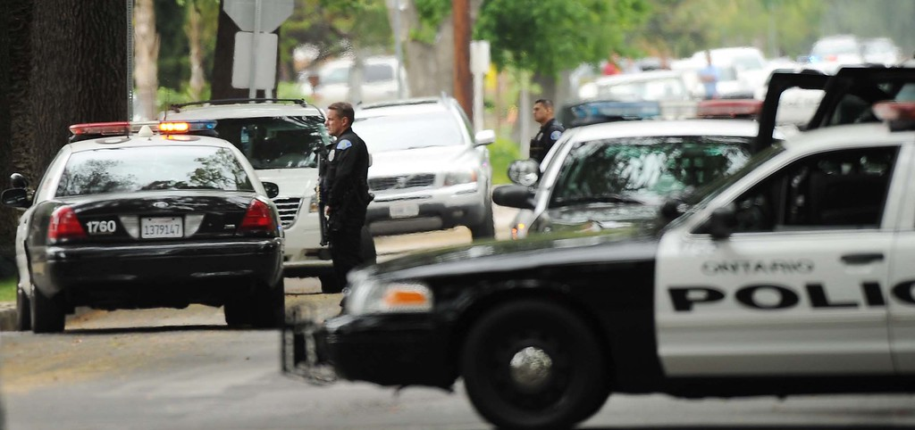 Description of . Ontario Police officers search for an allegedly armed man in the 100 block East Harvard Place near Euclid Avenue Sunday in Ontario. (LaFonzo Carter/Staff Photographer)