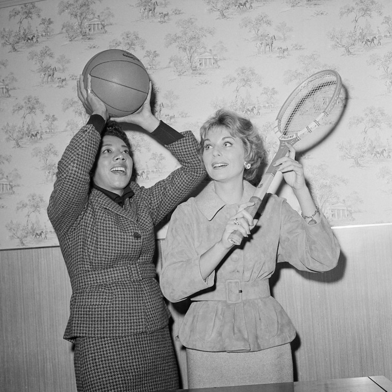 Description of . Althea Gibson, left, and Karol Fageros are shown in New York, Oct. 19, 1959 where they signed a professional contract with the Harlem Globetrotters. Beginning Dec. 29 both women will make a nationwide tour with the Globetrotters playing exhibition matches prior to Globetrotter games. (AP Photo/Harry Harris)