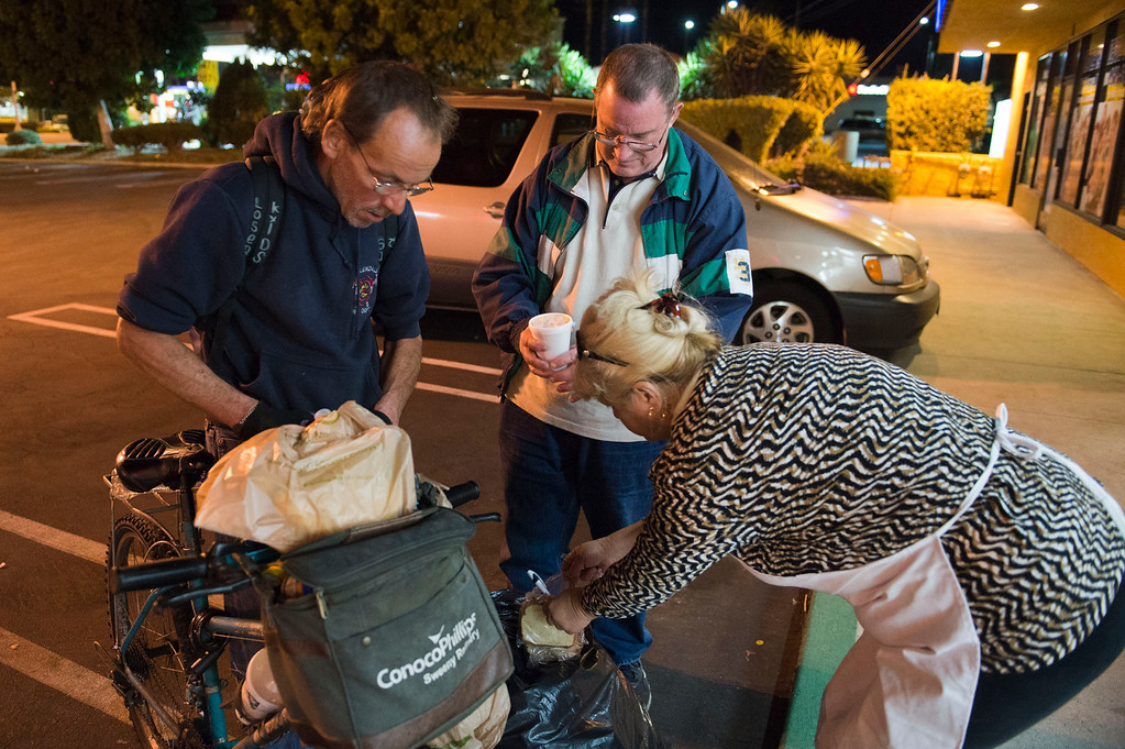 Description of . Nicolette Wingert, right, and Phillip Stern, center, give food and water to a homeless man in Glendora on Wednesday night, Nov. 27, 2013. Nicolette Wingert has been feeding the homeless six days a week for the past seven years with Nurses4Christ, a nonprofit organization she founded in 2006. She and Phillip Stern of Glendora have been going every day since 2008, feeding homeless people sandwiches and hot food; giving them bottles of water, clothes and blankets. (Photo by Watchara Phomicinda/San Gabriel Valley Tribune)