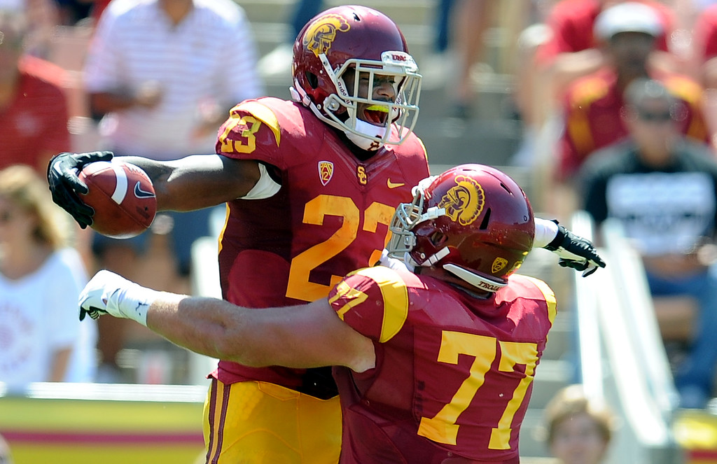 Description of . Southern California running back Tre Madden (23) reacts with teammate offensive tackle Kevin Graf (77) after catching a 5 yard touchdown pass against Boston College during the first half of an NCAA college football game in the Los Angeles Memorial Coliseum in Los Angeles, on Saturday, Sept. 14, 2013.