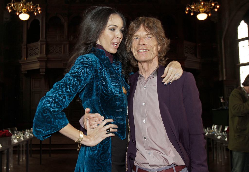 Description of . FILE - This Feb. 16, 2012 file photo shows singer Mick Jagger, right, with designer L'Wren Scott after her Fall 2012 collection was modeled during Fashion Week, in New York. Scott was found dead Monday, March 17, 2014, in Manhattan of a possible suicide. (AP Photo/Richard Drew, File)