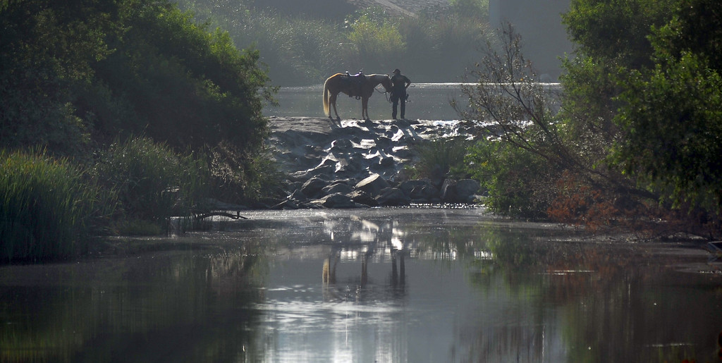 Description of . A Los Angeles County Sheriff's Mounted Deputy stops on the trail as they search for homeless individuals camping in the river bed area of the San Gabriel River near South El Monte on Thursday September 12, 2013. (Whittier Daily News/Staff Photo by Keith Durflinger)