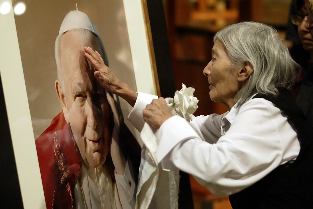 Description of . (4-1-05 Los Angeles) Floresita Hernandez touches  a portrait of Pope John Paul the II after a special mass at  Our Lady of Angels Cathedral for the pontiff. Pope John Paul II died on April 2, 2005.   (Hans Gutknecht/LA Daily News)