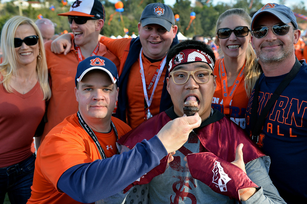 Description of . Auburn fans have fun with a Florida State friend before the BCS game at the Rose Bowl, Monday, January 6, 2014. (Photo by Michael Owen Baker/L.A. Daily News)