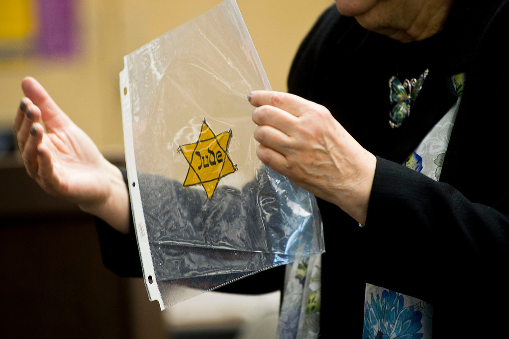 Description of . Inge Auerbacher, 78, one of the Holocaust child survivors, holds at the Star of David that she wore as a child in the Holocaust as she speaks to students at Sierra High School in Glendora on Tuesday, Nov. 12, 2013. Auerbacher told her stories about the time she spent in the Terezin concentration camp. (Photo by Watchara Phomicinda/San Gabriel Valley Tribune)
