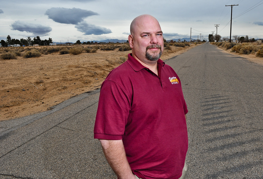 Description of . Barstow High School teacher and Hinkley resident Daron Banks, 44, stands in the middle of a desolate road in Hinkley, Calif. on Thursday, March 7, 2013. Banks is co-chairman of the Community Advisory Committee group that represents the residents' interest in PG&E related matters. (Rachel Luna / San Bernardino Sun)