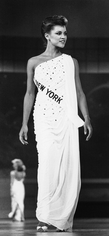Description of . Vanessa Williams, Miss New York, walks down the runway of The Miss America Pageant during her evening gown competition, Sept. 15, 1983 in Atlantic City. (AP Photo/Bruce Boyajian)