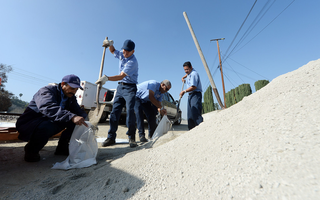 Description of . St. Lucy's Priory High School employees Jose Perez, Enrique Zavala, Frank Cephas and Santiago Verguzco fill sand bags at the Glendora city yard Tuesday February 25, 2014. Possible heavy rains in the coming days could create mud flows off of the burned hill sides caused by January's Colby Fire. (Will Lester/Inland Valley Daily Bulletin)