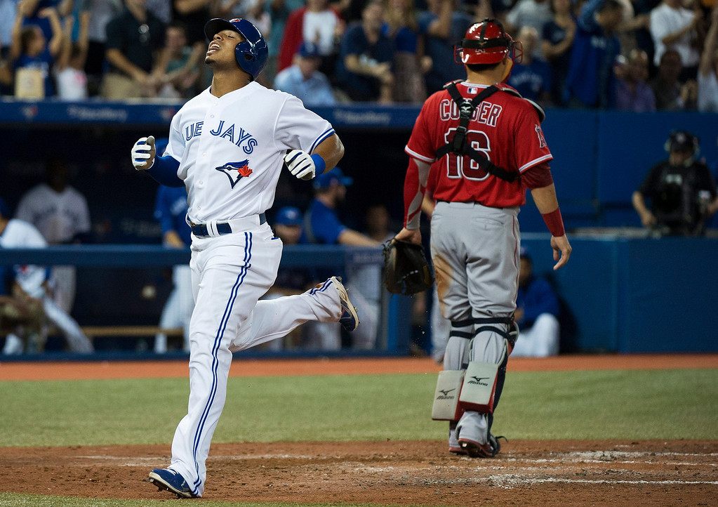 Description of . Toronto Blue Jays' Moises Sierra, left, reacts at home plate past Los Angeles Angels catcher Hank Conger, right, after hitting a triple but then advancing to home plate as there was an error at third base during fourth-inning AL baseball game action in Toronto, Wednesday, Sept. 11, 2013. (AP Photo/The Canadian Press, Nathan Denette)