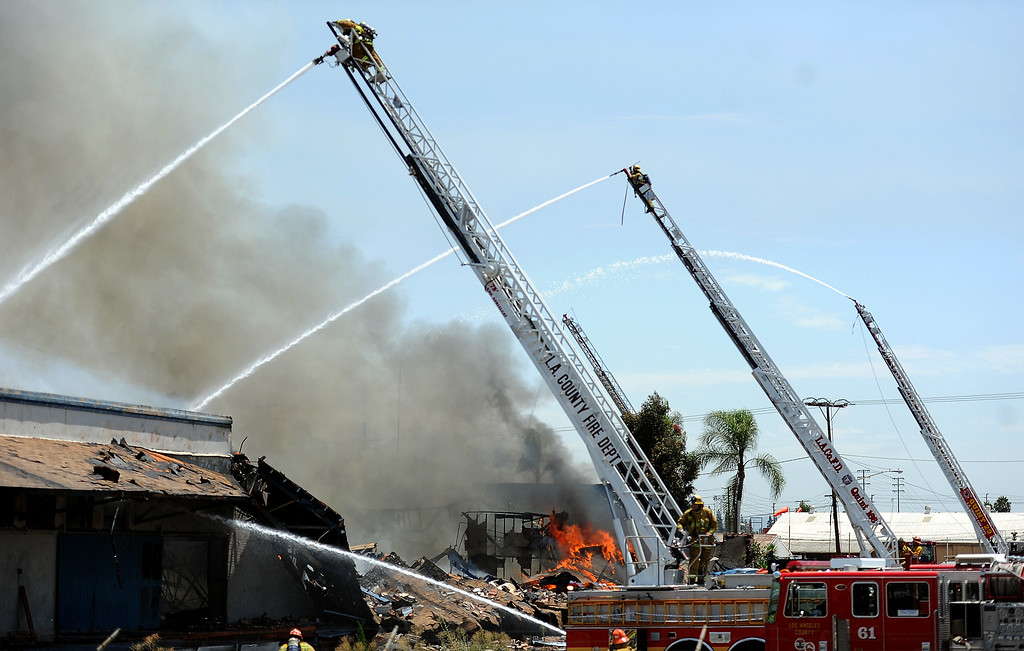 Description of . Los Angeles County firefighters battle a 3-alarm fire at an abandoned warehouse near 9th Avenue and Clark Avenue on Tuesday, July 9, 2013 in City of Industry, Calif.  (Keith Birmingham/Pasadena Star-News)